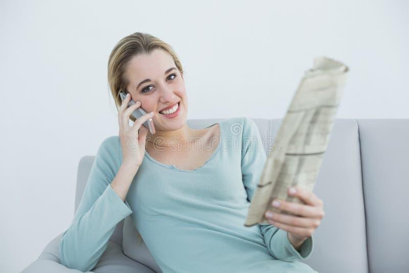 Lugna kvinna som ringer medan hållande tidning och sammanträde på soffan royaltyfri bild