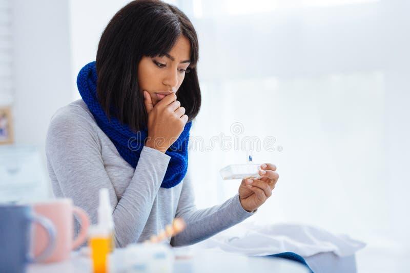 Lugna kvinna som uppmärksamt ser på preventivpillerasken arkivbilder
