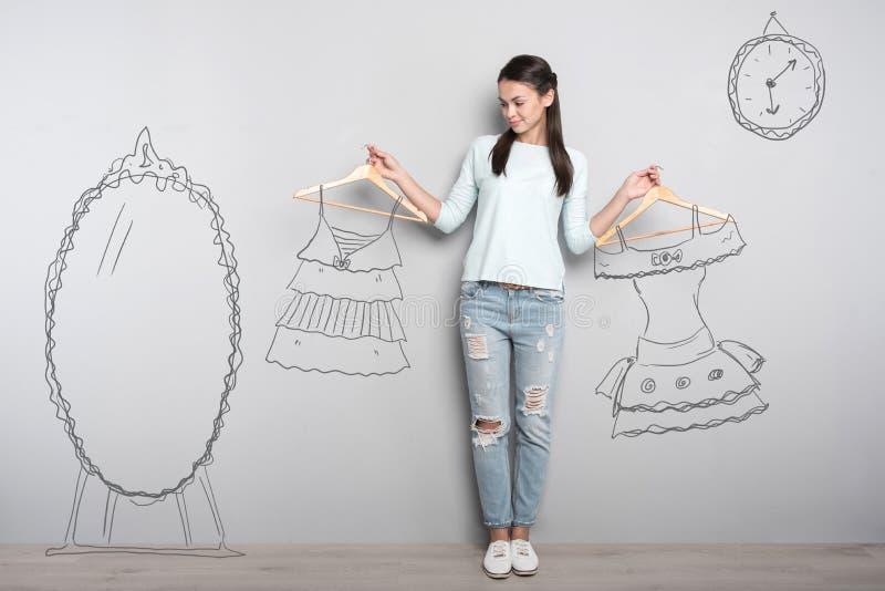 Lugna kvinnaanseende nära spegeln och drömma om ny kläder arkivfoton