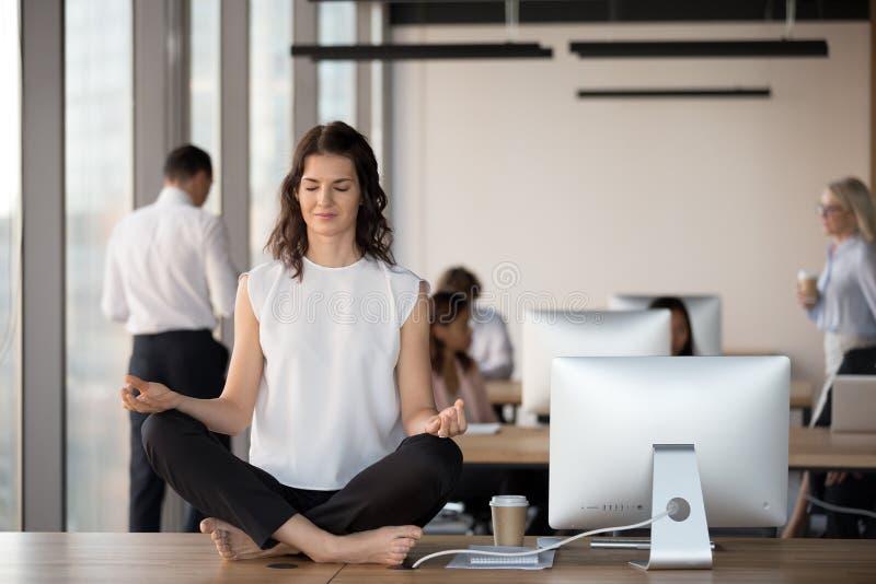Lugna kvinnlig anställdövningsyoga på tabellen i coworking utrymme royaltyfri bild