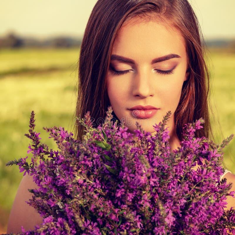 Lugna och avkopplad härlig kvinna som är utomhus- med blommor i händer arkivfoton