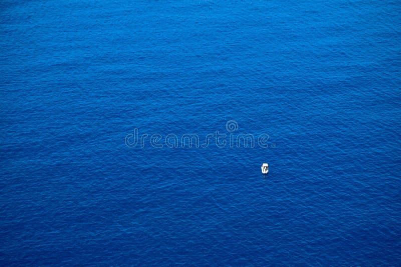 Lugna plan yttersida av havet och det lilla fisherfartyget driva som fiskar medelhavs- netto havstonfisk royaltyfria foton
