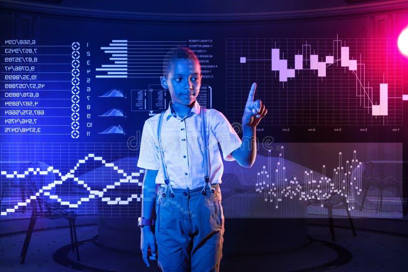 Lugna pojke som har IT-kurser och trycker på försiktigt en genomskinlig apparat arkivfoton