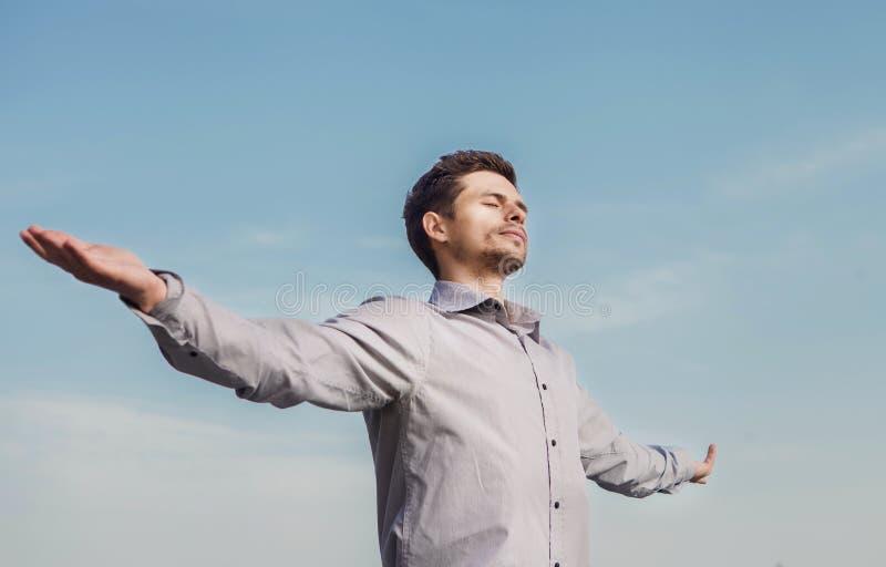 Lugna stående för ung man över blå himmel royaltyfri bild