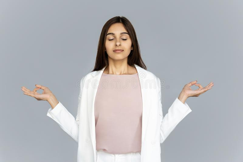 Lugna sund indisk affärskvinna som mediterar på grå studiobakgrund royaltyfri foto