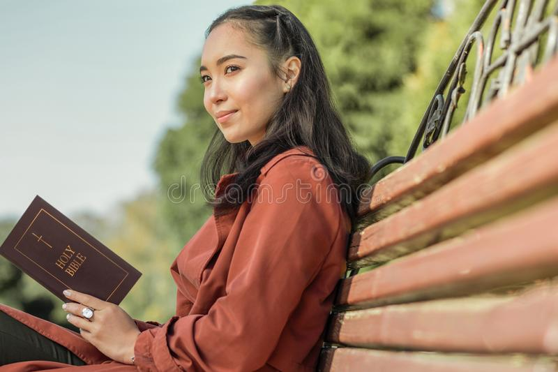 Lugna ung kvinna med det mjuka leendet som fokuseras på en bibel royaltyfri fotografi