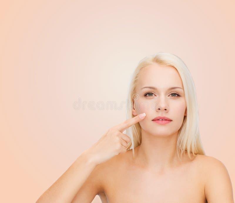 Lugna ung kvinna som pekar på hennes kind arkivbild