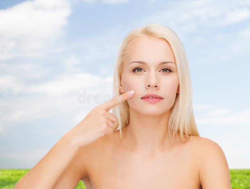 Lugna ung kvinna som pekar på hennes kind fotografering för bildbyråer