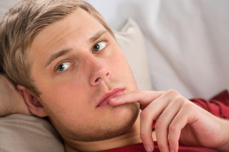 Lugna ung man som lägger på soffan och att tänka arkivbild