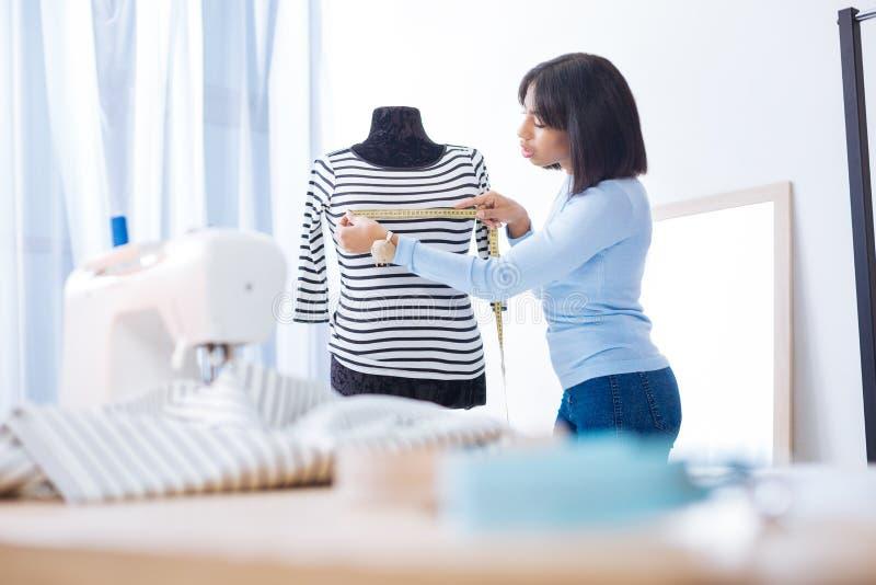 Lugna uppmärksam skräddare som kontrollerar längden av en blus och ser allvarlig royaltyfri bild