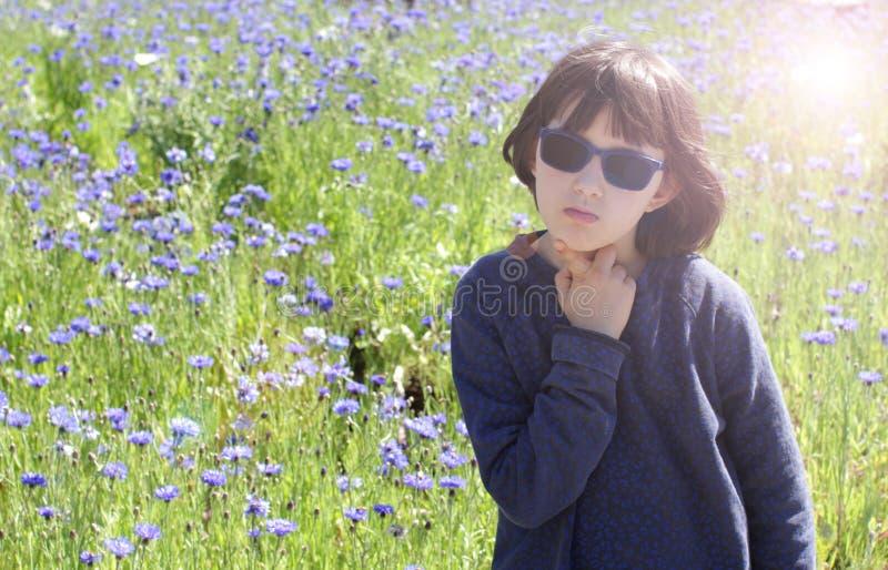Lugna uttråkat barn med solglasögon som dagdrömmer, solgloriaeffekt royaltyfri foto