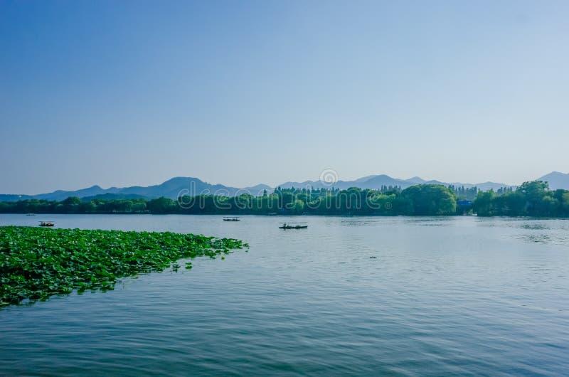 Lugna vatten av den västra sjön och omgeende kullar, med fartyg som reser på vatten, i Hangzhou, Kina royaltyfria bilder