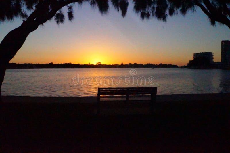 Lugna vatten som håller ögonen på solnedgång arkivbild
