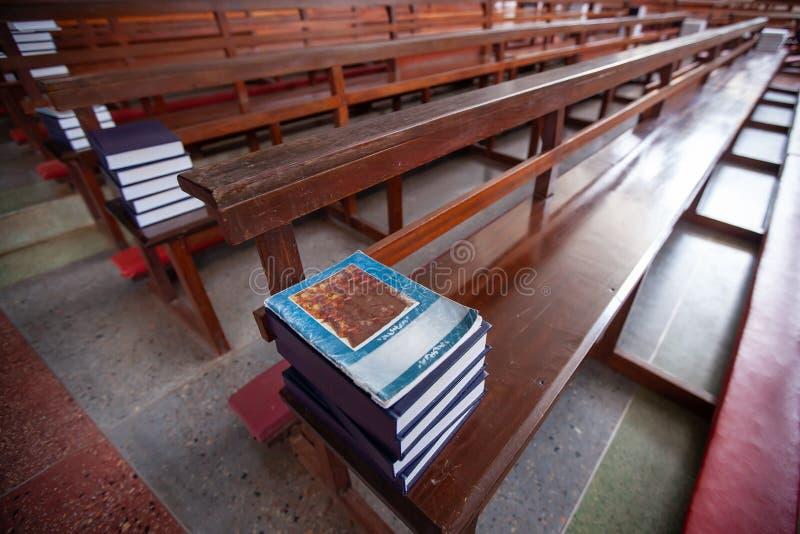 Lugnstället, den thailändska katolska bönboken är på raderna av träkyrkliga bänkar, mjuka stråla ljusa sken i kyrkan royaltyfria foton