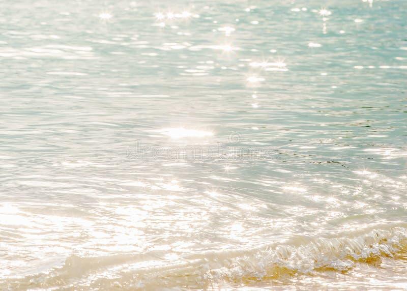 Lugntid, härlig yttersida av havsvatten i morgonen, ljus blänka stjärnabokeh, mjuka vågor och bubbla tropiskt hav arkivbild