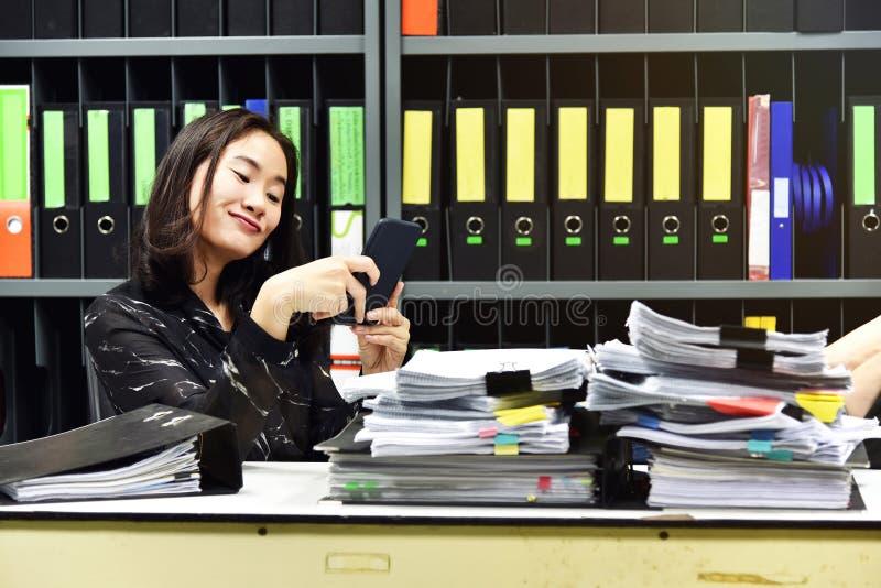 Luie Aziatische bureauvrouw die mobiele slimme telefoon in werktijd met behulp van stock foto's