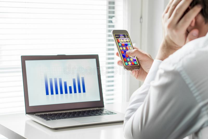 Luie beambte die mobiel spel met smartphone spelen stock foto