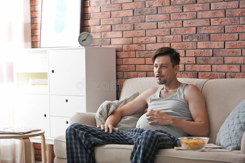 Luie mens die met kom van spaanders op TV letten stock fotografie
