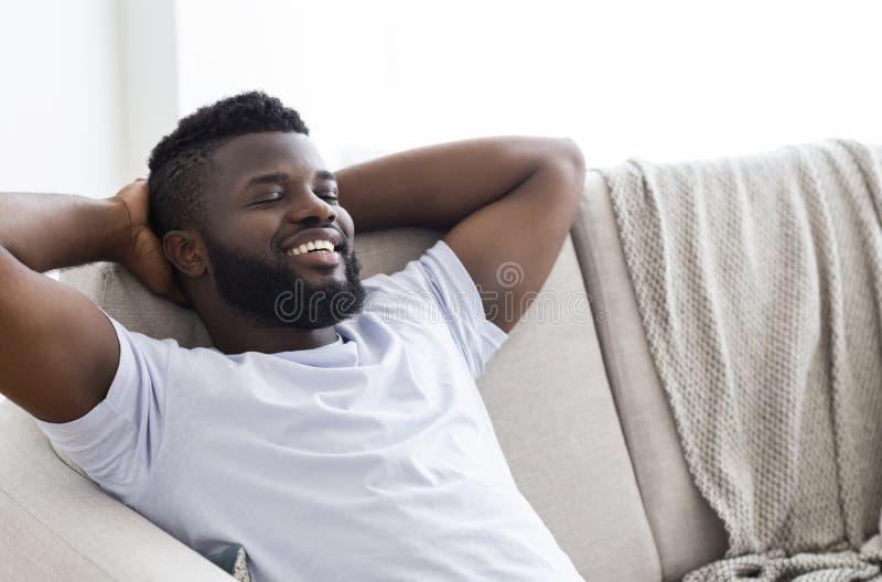 Luie millennial Afrikaanse Amerikaanse kerel die thuis ontspannen stock afbeeldingen