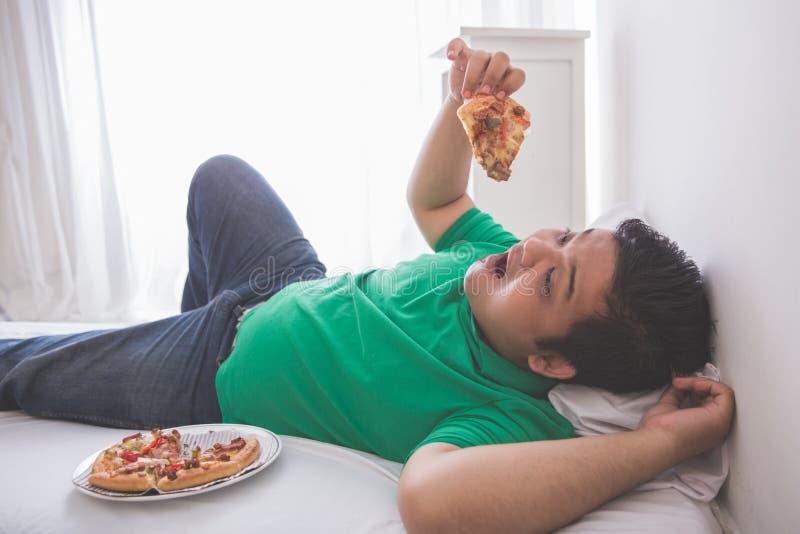 Luie te zware mens die pizza eten terwijl het leggen op een bed royalty-vrije stock fotografie
