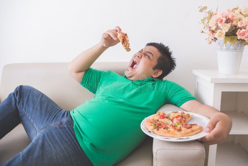 Luie te zware mens die pizza eten terwijl het leggen op een laag stock foto's