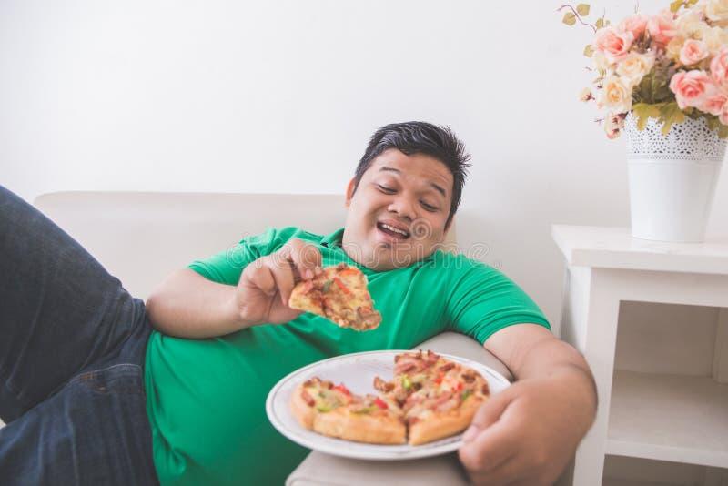 Luie te zware mens die pizza eten terwijl het leggen op een laag royalty-vrije stock afbeeldingen