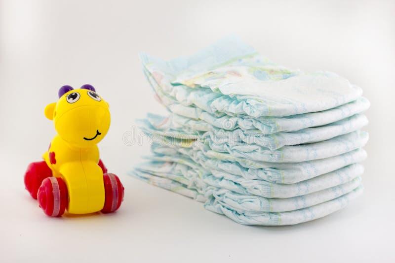 Luiers en een kinderen` s stuk speelgoed op een witte zuigeling als achtergrond stock foto