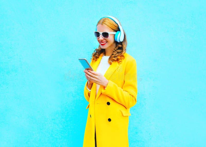 Luistert de manier mooie glimlachende vrouw die smartphone gebruiken aan muziek stock foto