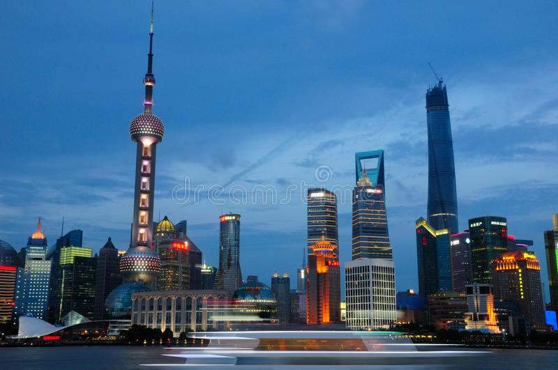 Lujiazui at night. Lujiazui lit up at night as seen from across the Huangpu river at the Bund, with a boat traveling by. Pearl tower, shanghai Tower and royalty free stock image