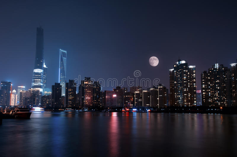 Lujiazui Skyline at Night. Lujiazui skyline lit up under a waxing moon at night across the Huangpu River royalty free stock images