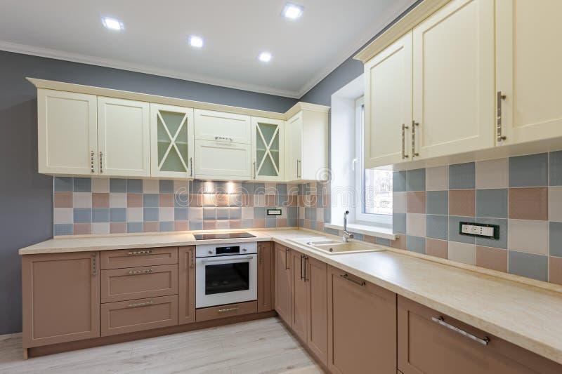 Lujosa cocina moderna en tonos grises, rosa y crema fotos de archivo