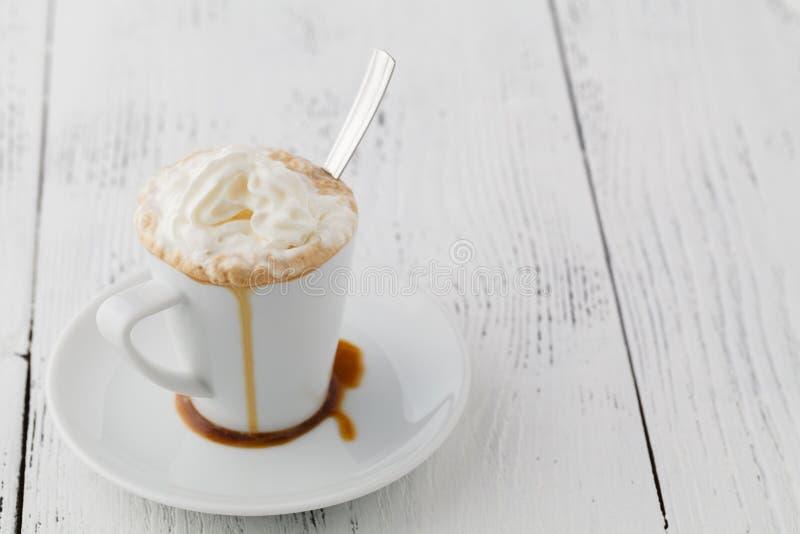 Lukrowa kawa z batożącym mleka i karmelu lody w wysokich szkłach na nieociosanym drewnianym stole, selekcyjna ostrość obraz royalty free