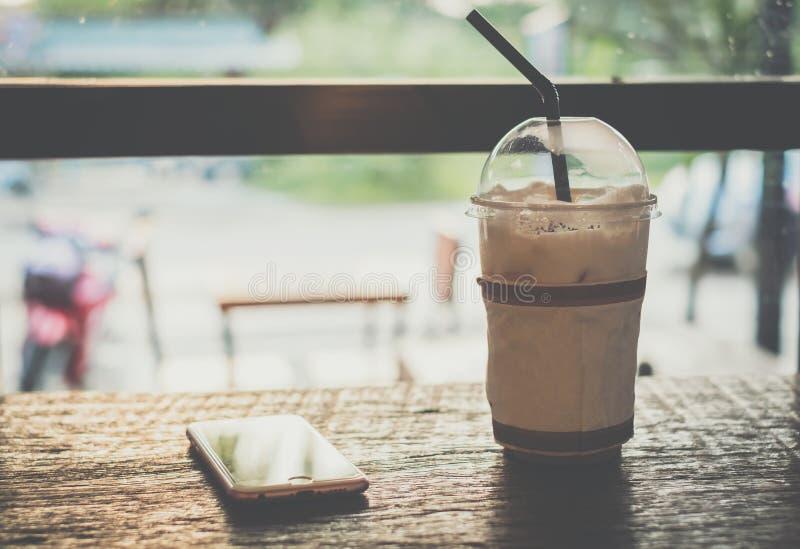 Lukrowy kakao, czekolada, z bat śmietanką w Plastikowej filiżance i telefonie komórkowym na drewnianym stole obrazy royalty free