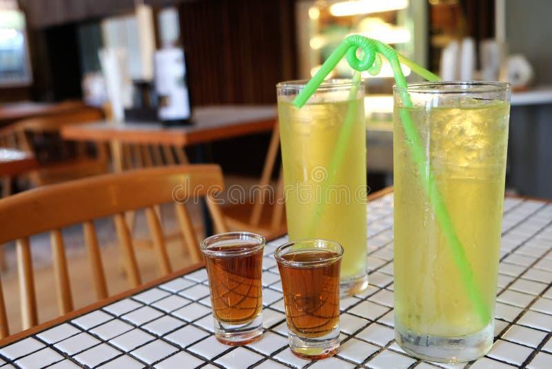 Lukrowy zimny zielona herbata napój w szkle i fantazji zielonej słomie z syropem w strzału szkle na biel płytki stole zdjęcia royalty free