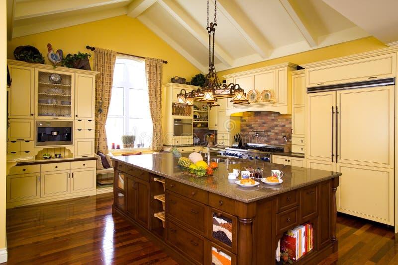 Luksusowa żółta drewniana kuchnia z brown wyspy i granitu wierzchołkiem zdjęcia royalty free