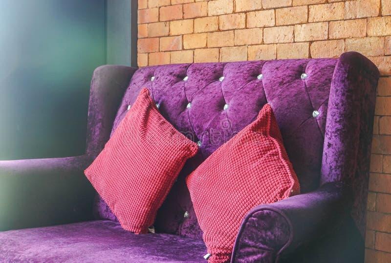 Luksusowa aksamitna fiołkowa kanapa z czerwieni poduszką dla siedzenia obraz stock
