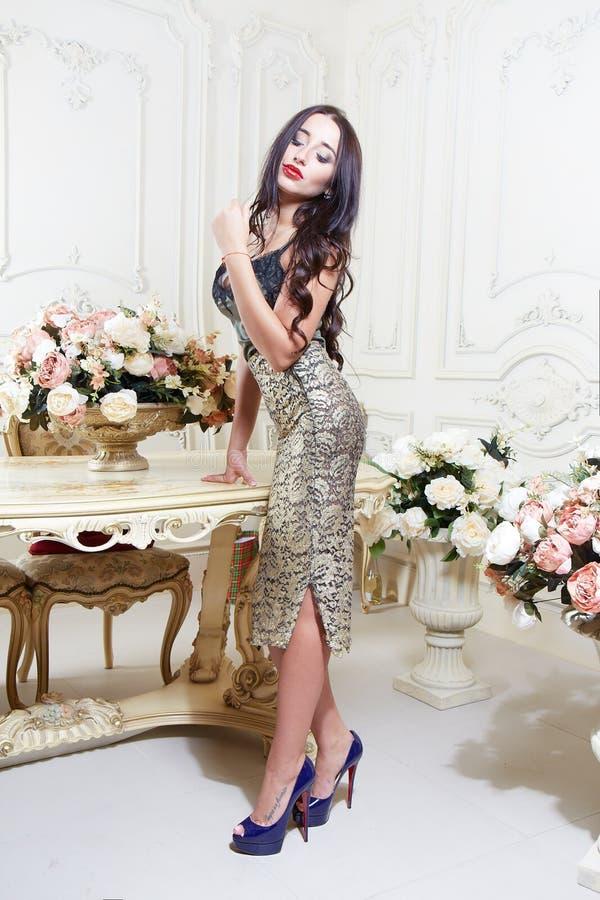 Luksusowa kobieta z długiej brunetki kędzierzawym włosy i czerwonymi wargami w złoto sukni pozuje w szpilkach i pracownianym pobl fotografia royalty free
