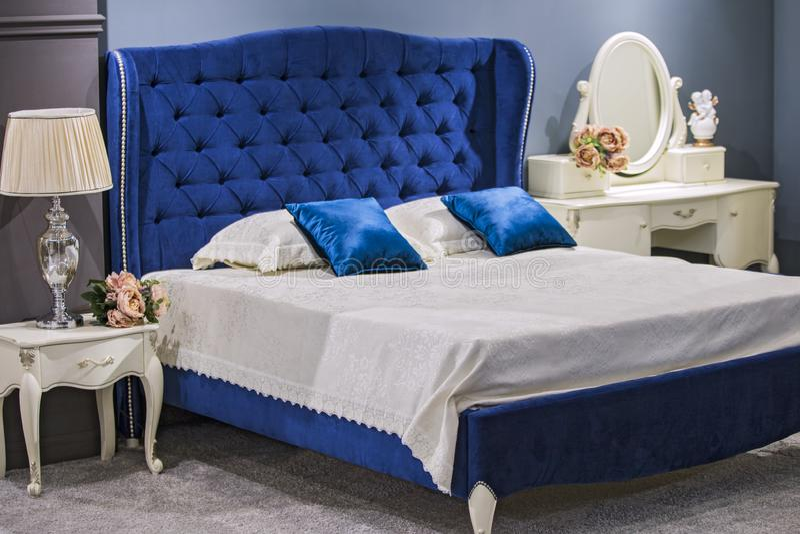 Luksusowa królewska sypialnia w antyka stylu z błękitnym aksamitnym łóżkiem i białym nightstand obrazy royalty free