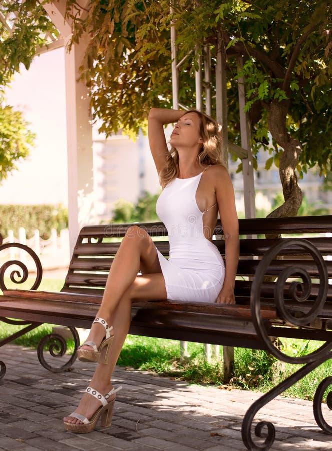 Luksusowa pi?kna szczup?a blondynka w seksownej sukni biel heeled sanda?ach i siedzi na ?awce w parku zdjęcie royalty free