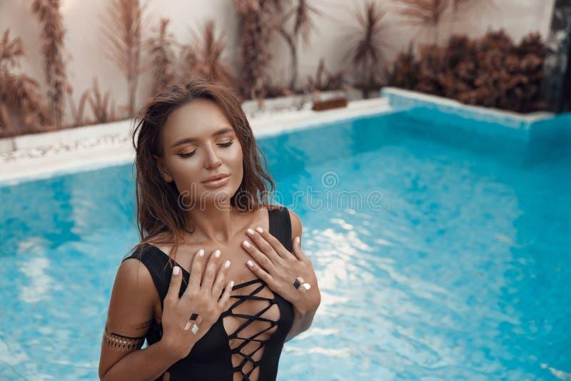 Luksusowa podróż bikini dziewczyna z seksownym ciałem w czarnym swimwear pozuje basenem przy luksusową willą Wysokiej mody kolory obraz royalty free
