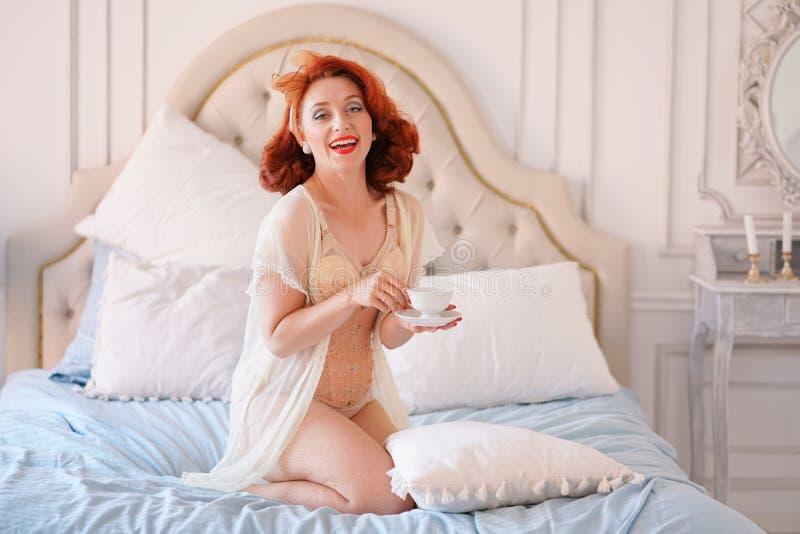 Luksusowa szpilka w górę damy ubierającej w beżowej rocznik bieliźnie pozuje w jej sypialni i filiżankę śniadaniowa herbata obrazy stock