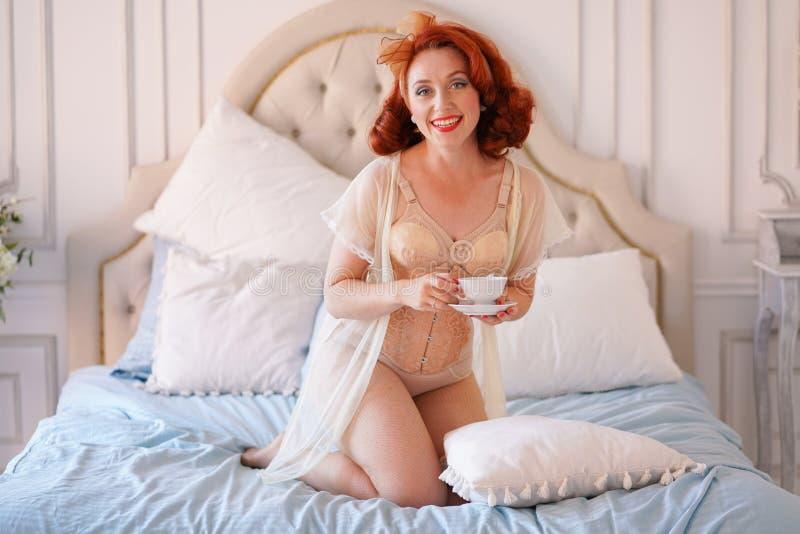 Luksusowa szpilka w górę damy ubierającej w beżowej rocznik bieliźnie pozuje w jej sypialni i filiżankę śniadaniowa herbata zdjęcia stock