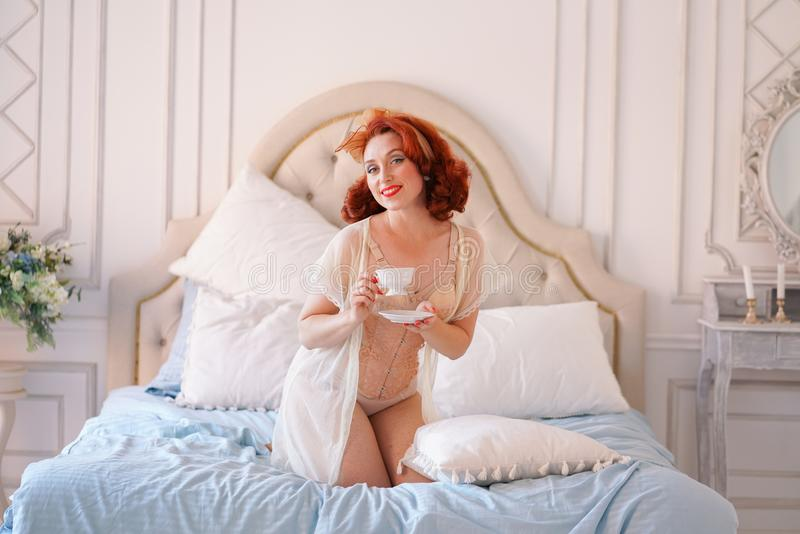 Luksusowa szpilka w górę damy ubierającej w beżowej rocznik bieliźnie pozuje w jej sypialni i filiżankę śniadaniowa herbata obraz stock
