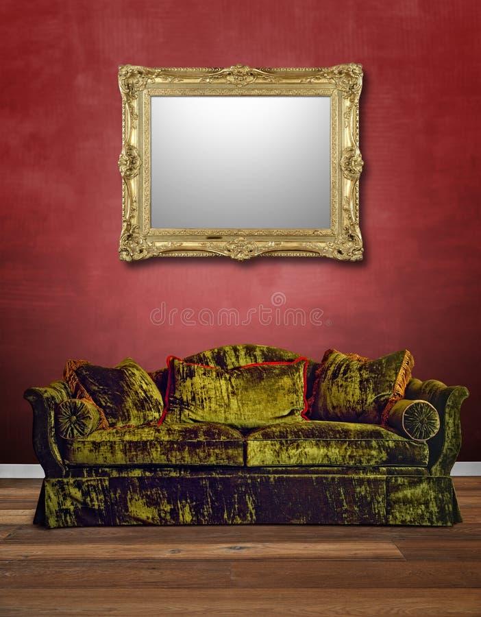 Luksusowa zielona aksamitna kanapa z textured czerwieni ścianą obraz stock