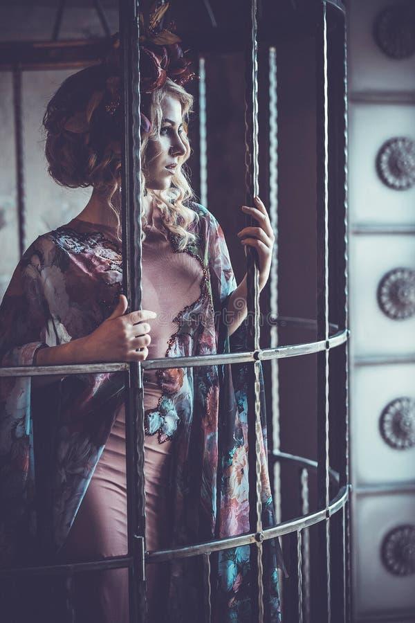 Luksusowej mody elegancka dziewczyna w klatce Kwiat suknia i wr fotografia stock