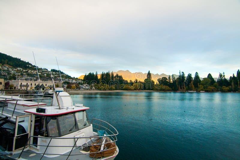 Luksusowy łódkowaty dok w Queenstown Nowa Zelandia turystycznym miejsce przeznaczenia z złotym zmierzchem zaświeca na Remarkables fotografia stock