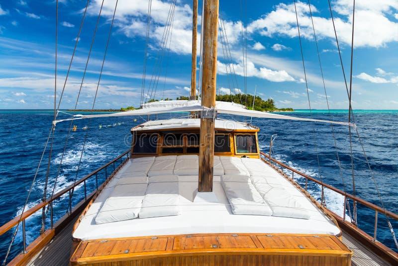 Luksusowy żeglowanie łodzi jacht przed tropikalnym rajów Maldives wyspy kurortem z rafą koralową i błękitny ocean nawadnia obrazy stock