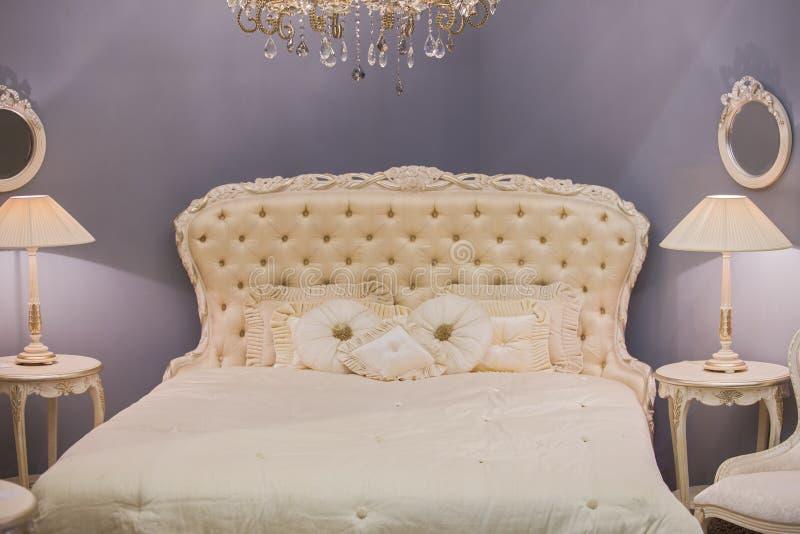 Luksusowy drogi wewnętrzny projekt dziecka ` s dziewczyny pokój w starym stylu Biały łóżko, jedwabnicze poduszki, wezgłowie stoły obrazy stock