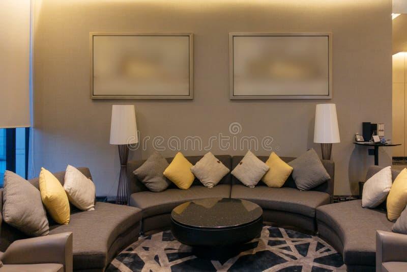 Luksusowy nowożytny żywy pokój z poduszkami, meble, obrazek ramą i kanapy dekoracją przy nocą, Domowy wewnętrznego projekta tło zdjęcia stock