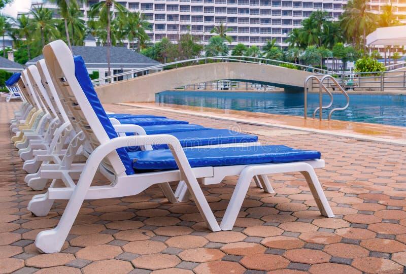 Luksusowy pływacki basen z białymi deckchairs zdjęcia stock